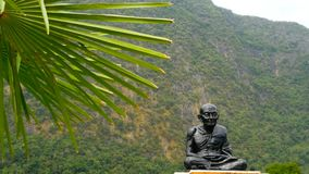 Monument to the monk, a tourist place in the south Thailand. Statue of a sitting black monk. Part of the public temple complex at the foot of the mountain stock footage