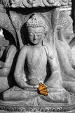 Statue of a sitting deity with  butterfly Stock Photo
