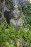 Statue sitting in lotus ascetic in the green grass. A Asian statue in The Grand Palace in Bangkok, Thailand Royalty Free Stock Photo