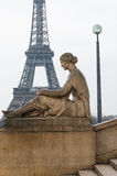Statue of sitting woman and Eiffel Tower Royalty Free Stock Photo