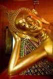 Statue of sleeping Buddha. Covered in gold paint and gold leaf in a local Thai temple Stock Photography