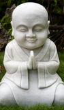 Statue of smiling monk praying Stock Images