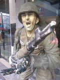 Statue of soldier holding gun. Statue of a soldier in US Army fatigues with helmet holding a gun outside a modern building Stock Image