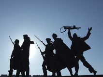 Statue of the soldiers. Silhouette of a monument to soldiers, against the sun Royalty Free Stock Photography