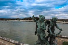 Statue sotto cielo blu fuori del palazzo di Versailles fotografia stock libera da diritti