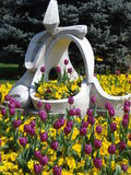 Statue among spring flowers. Statue on green area near Victoria square in Bucharest Stock Photos