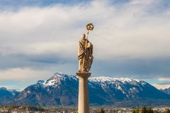 Statue of St.Benedict in front of Maria Plain pilgrimage church. In Berghein bei Salzburg, Austria. Untersberg mountain on the background Royalty Free Stock Photo