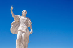 A statue of St Elijah the prophet holding a knife on a blue sky Stock Photo