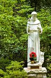 Statue of St. Francis. A view of a small statue of Saint Francis of Assisi in a natural setting in the woods at the The National Shrine Grotto of Lourdes stock image