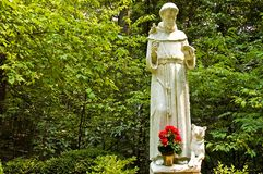 Statue of St. Francis. A view of a small statue of Saint Francis of Assisi in a natural setting in the woods at the The National Shrine Grotto of Lourdes royalty free stock photo