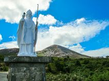 Statue of St. Patrick in front of Crough Patrick Mountain stock photography