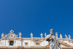 Statue of St. Peter, St. Peter Basilica and statues standing on the roof of St. Peter Basilica on the background, Va Royalty Free Stock Photos