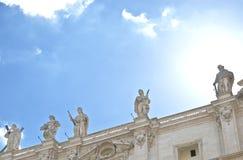 Statue sul tetto di St Peter & di x27; basilica di s Sopra la testa di una delle sculture il sole splende e ricorda all'alone Immagine Stock