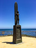 Statue of surfer on a plinth. Bronze statue  of a surfer with surf board standing on a decorated plinth overlooking a calm blue sea at Santa Cruz California Royalty Free Stock Photos