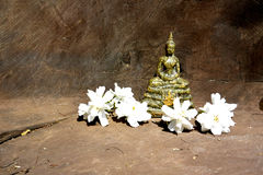 Statue of Thai Buddha in meditation pose with white flowers. Thai meditation Buddha statue. The meditation Buddha is one of the most common iconic images of stock photo