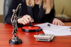 The statue of Themis on desk. The statue of Themis on the background of a working woman - notary public stock image