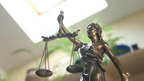 Statue of Themis or Lady Justice on Bookshelf Background