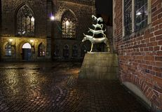 Statue of the Town Musicians of Bremen at night with the historic city hall and the Church of our Lady in the background royalty free stock images