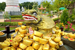 Statue and traditional chinese ancient gold bullion nugget. Royalty Free Stock Photos