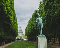Statue between trees with Pantheon in the distance, in Luxembourg Gardens in Paris, France. View of statue between trees with Pantheon in the distance, in royalty free stock photos