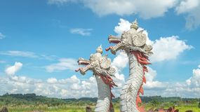 Statue of twin dragon with beautiful sky as the background in Pulau Kumala, Indonesia. Statue of twin dragon, mythological creatures from Kutai tribe in Pulau Royalty Free Stock Images
