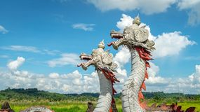 Statue of twin dragon with beautiful sky as the background in Pulau Kumala, Indonesia. Statue of twin dragon, mythological creatures from Kutai tribe in Pulau Stock Photos