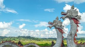 Statue of twin dragon with beautiful sky as the background in Pulau Kumala, Indonesia. Statue of twin dragon, mythological creatures from Kutai tribe in Pulau Royalty Free Stock Photos