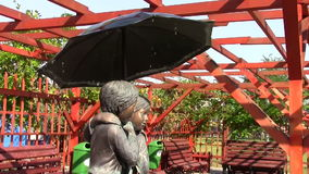Statue with two children. Under the umbrella stock video footage