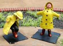 Statue of Two Young Children Splashing And Stomping In The Rain. Statue of Two Young Child wearing a raincoats and boots and playing, stomping,  splashing and Stock Image