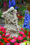 Statue of two young lovers in the garden. Spring garden view with statue of two young lovers in a intimate position Royalty Free Stock Photography