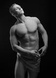 Statue und Make-upkörperthema: aufgeblähter Mann mit den großen Muskeln, die in der weißen Farbe gemalt werden, ist auf einem dun Lizenzfreie Stockfotos