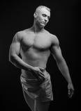 Statue und Make-upkörperthema: aufgeblähter Mann mit den großen Muskeln, die in der weißen Farbe gemalt werden, ist auf einem dun Stockfotos