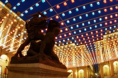 Statue under artistic lights. Palazzo di Città square at dusk with Christmas artistic lights in Turin, Italy Royalty Free Stock Images