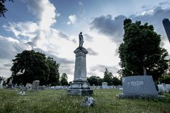 Statue under cloudy sky. A statue and headstones stand under a cloudy sky in an old Cemetery in Rochester, New York, July 2018 Royalty Free Stock Images