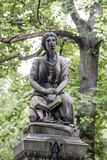 Statue under trees. A statue stands under trees in an old Cemetery in Rochester, New York, July 2018 Royalty Free Stock Photos