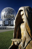 Statue- Vancouver, Canada. Wooden statue in front of gleaming geodesic dome of Science World illluminated at dusk with skyscrapers of downtown in background Royalty Free Stock Images