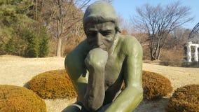 Statue verte de penseur Auguste Rodin, plaçant nu sur une roche images stock