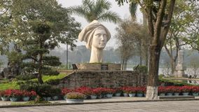 The statue of a Vietnamese girl, sculpted by Le Thanh Nhon, located in Hue along the Parfume River. Pictured is a `The statue of a Vietnamese Girl`, sculpted royalty free stock image