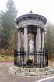 Statue of the virgin and baby Jesus under a monument in the fore Royalty Free Stock Photos