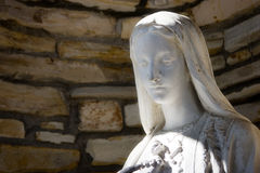 Statue of the Virgin Mary. Against stone backdrop Royalty Free Stock Images