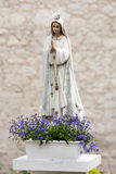 Statue of Virgin Mary with flowers Royalty Free Stock Images