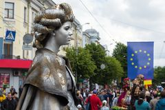 Statue vivante de la reine dans la perspective des personnes, des bâtiments et du drapeau de l'Union européenne photographie stock