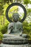 Statue von Buddha mit Bäumen im Hintergrund Stockbild