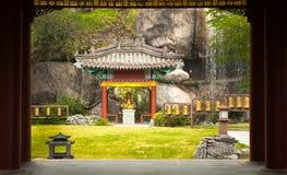 Statue von Buddha sitzend am Rand des Gartens Stockfotografie
