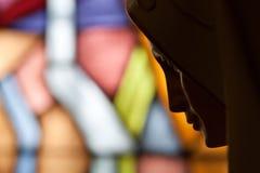 Statue von heiligem Mary auf Buntglas Stockfotografie