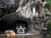 Statue von Jungfrau Maria in der Grotte von Lourdes zieht viele an Lizenzfreie Stockfotos