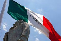 Statue von Manuel Jose anderer mit der mexikanischen Flagge im Hintergrund lizenzfreie stockbilder