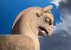 Statue von Vogel Huma oder Homa als dekorativem Spaltenkopf in Persepolis gegen blauen Himmel mit weißen Wolken Lizenzfreie Stockfotos