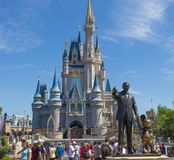 Walt Disney and Mickey mouse statue in front of Cinderella princess castle at Disney world Florida. Statue of Walt disney and mickey mouse lovely blue sky Royalty Free Stock Photos