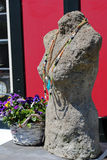 Statue wearing necklace. S with flowers in the background royalty free stock image
